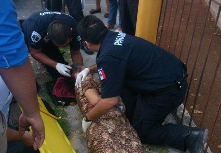 Imagen de los paramédicos al aplicar los primeros auxilios a la pasajera lesionada. El conductor del camión quedó detenido. (Milenio Novedades)