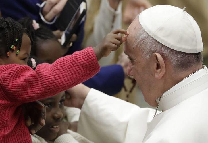 El Papa Francisco acaricia a un niño durante su audiencia semanal en el Vaticano, el miércoles 4 de enero de 2016. (AP/Andrew Medichini)