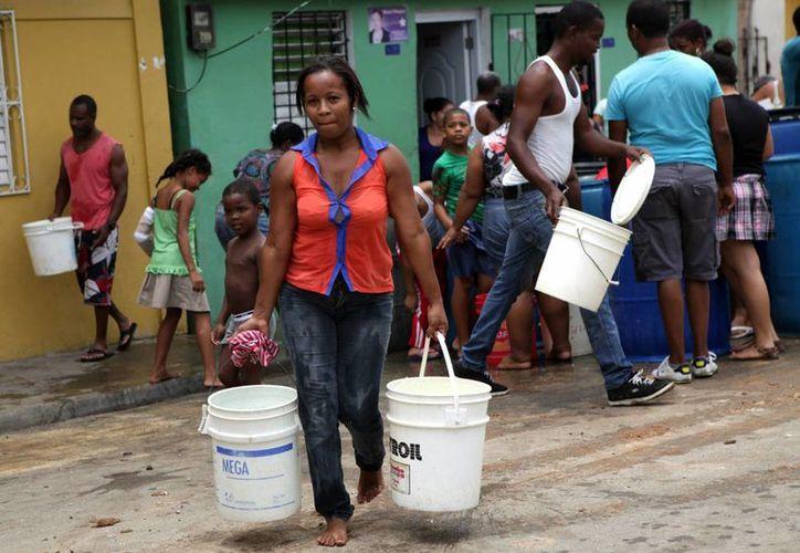 Habitantes de diversos barrios de Santo Domingo (República Dominicana) fueron registrados este martes al recibir agua repartida por el gobierno. (EFE)