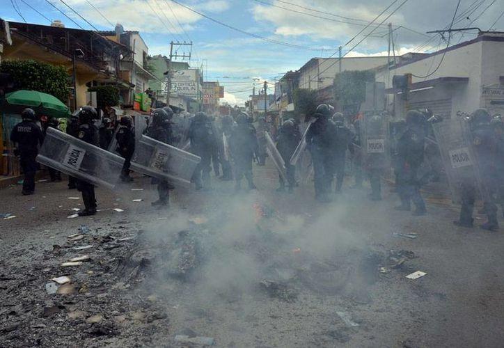 La policía y el Ejército tomaron el control de acceso a las intalaciones del INE, en Oaxaca, luego de que los maestros de la CNTE abandonaran los plantones que mantenían en las sedes. La imagen no corresponde al hecho, sino a los desmanes que profesores de la Coordinadora provocaron en Chilpancingo, Guerrero, en donde quemaron boletas electorales. (AP)