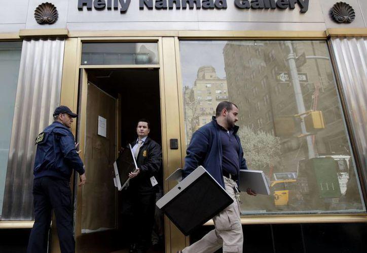 Agentes federales sacan computadoras y otros artìculos de una galería de arte en Nueva York como parte de la investigación.  (Agencias)