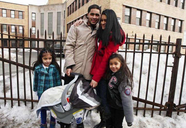 El hondureño Carlos Oliva-Guillen, junto a su novia, Emily Navas, y a sus hijos, posa para los fotógrafos después de ser liberado de un centro Control de Aduanas e inmigración en Newark. (EFE)