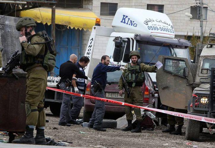 Dos personas murieron luego de un tiroteo contra un bar de Tel Aviv. En la imagen, integrantes de las fuerzas de seguridad israelíes inspeccionan un vehículo tras un ataque en la localidad de Huwara, cerca de la ciudad cisjordana de Nablus, ayer, 31 de diciembre de 2015. (Archivo/EFE)