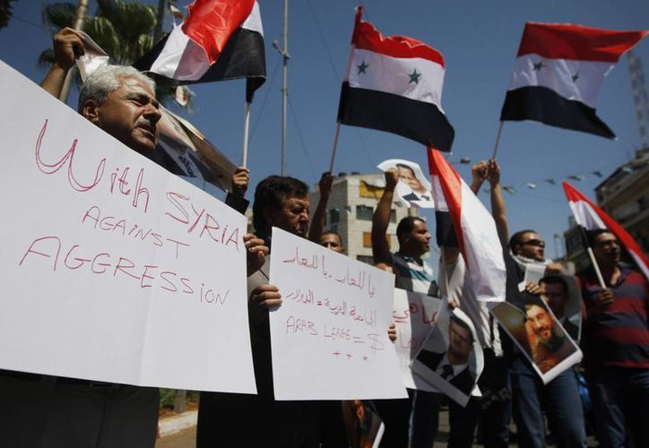 Palestinos en Ramallah sostiene símbolos y la bandera siria durante una protesta contra un posible ataque de EU. (Agencias)