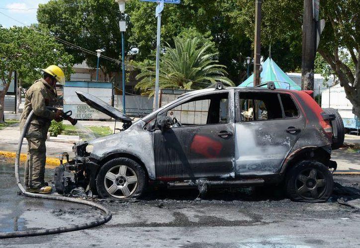 Al dar vuelta en una glorieta de la colonia María Luisa, el guiador se dio cuenta que su auto se incendiaba. (Fotos. SIPSE)