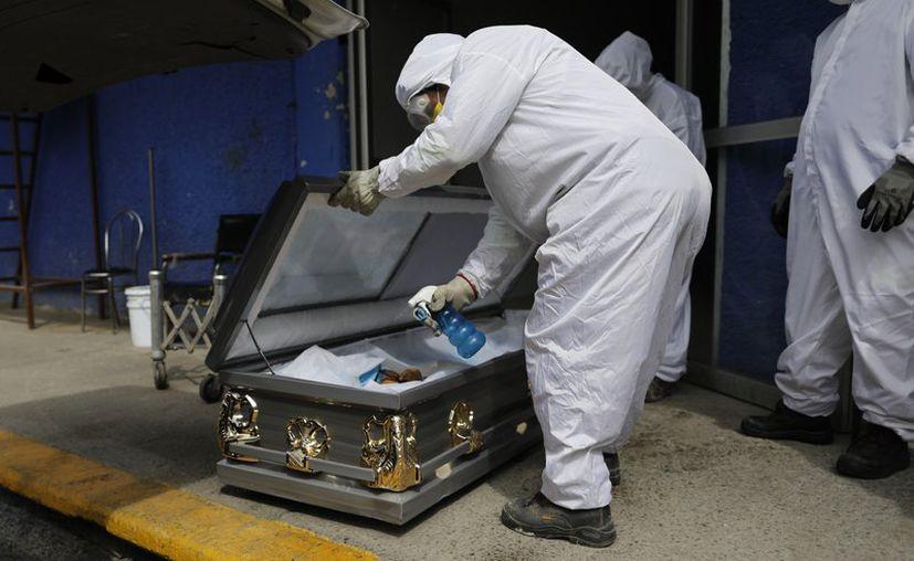 Un trabajador con equipo especial de protección rocía desinfectante dentro del ataúd de una persona que presuntamente falleció de COVID-19 en la Ciudad de México. (Foto: AP).