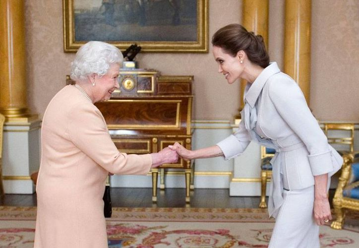 La actriz Angelina Jolie saluda a la Reina Isabel II, de quien recibió el nombramiento de 'dama de honor'. (AP)