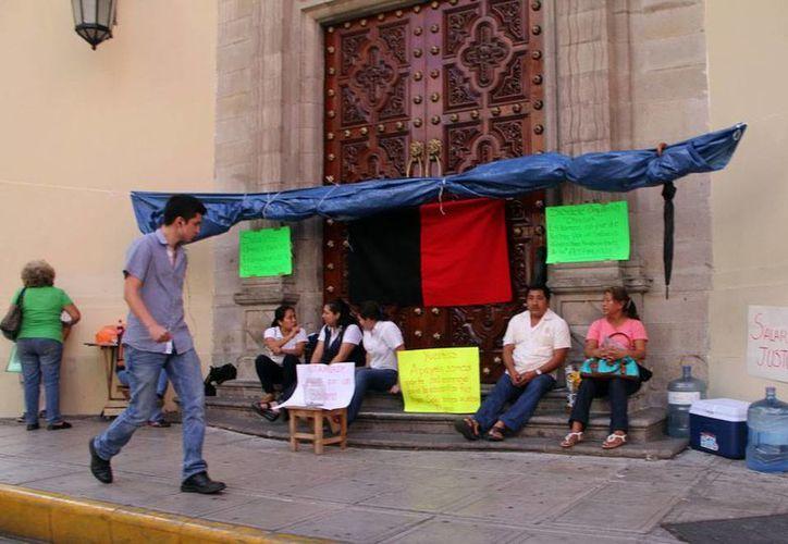 Trabajadores de la Uady montan guardia a la afuera del edificio central, tal como lo hacen también en las demás instalaciones de la Universidad, tras declararse en huelga. (José Acosta/SIPSE)