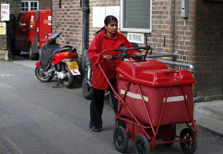 Una trabajadora postal sale del depósito del Correo en Londres. (Agencias)