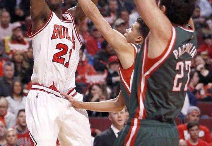 Jimmy Butler (21), de Bulls, lanza a la canasta pese a Michael Carter-Williams and Zaza Pachulia (27), de Bucks. (Foto: AP)
