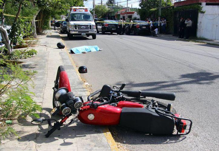 Un hombre que iba como pasajero en una moto murió tras estrellarse primero contra un auto y luego contra el pavimento. (Fotos: Pallota/SIPSE)