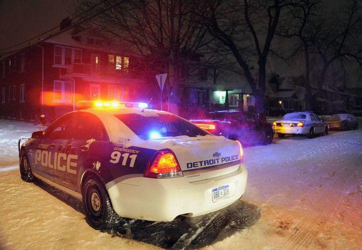 Una patrulla de la policía de Detroit estacionada en la casa donde un niño de cuatro años fue muerto accidentalmete de un disparo por su prima de igual edad con un fusil que encontró en casa del abuelo de ambos en Detroit. (Agencias)