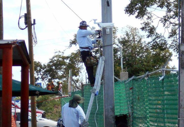 Imagen de un grupo de empleados al momento de realizar la instalación de una de las videocámaras en las afueras del reclusorio de Mérida. (Francisco Puerto/SIPSE)