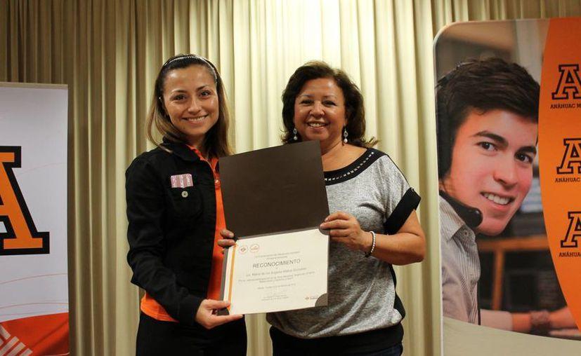 María de los Ángeles Matos González, directora de Infolaicos Mérida, recibe un reconocimiento por su participación en la Hora Newman, en la Universidad del Mayab. (Cortesía)