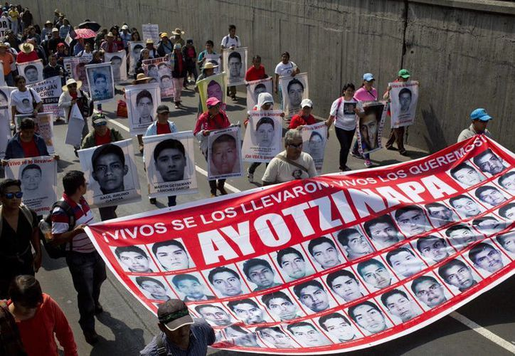 Familiares y manifestantes llevan pancartas con fotos de algunos de los 43 estudiantes de Ayotzinapa. Las marchas de protesta fueron planeadas en ciudades de todo México con motivo del cuarto mes desde su desaparición. (Agencias)