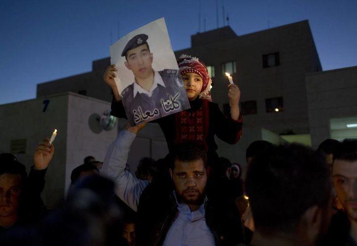 Un niño de Jordania sostiene una vela y una foto de piloto Muath al-Kaseasbeh, durante una vigilia en apoyo a Japón, frente a la embajada japonesa, en Ammán, Jordania. (Agencias)