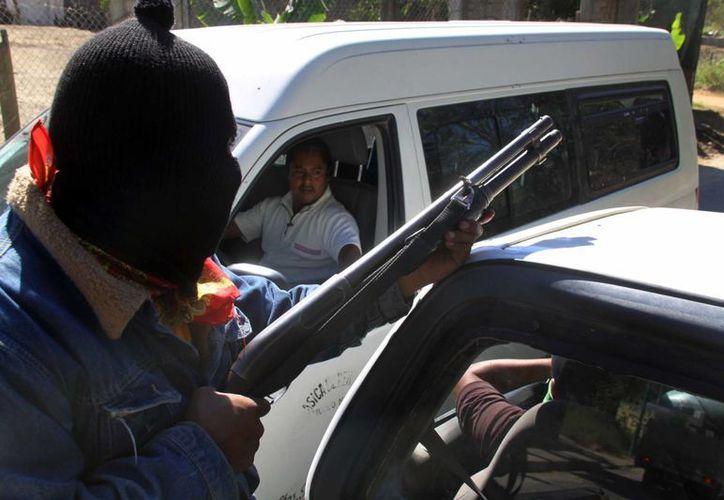 Vecinos revisan a los automovilistas que llegan a pueblo. (Notimex)