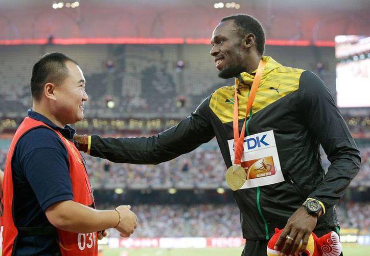 El camarógrafo que este jueves derribó al velocista Usain Bolt se reencontró con la estrella del Atletismo y, en señal de 'paz', se dieron la mano para demostrar que no hubo mayor problema con el incidente. (AP)
