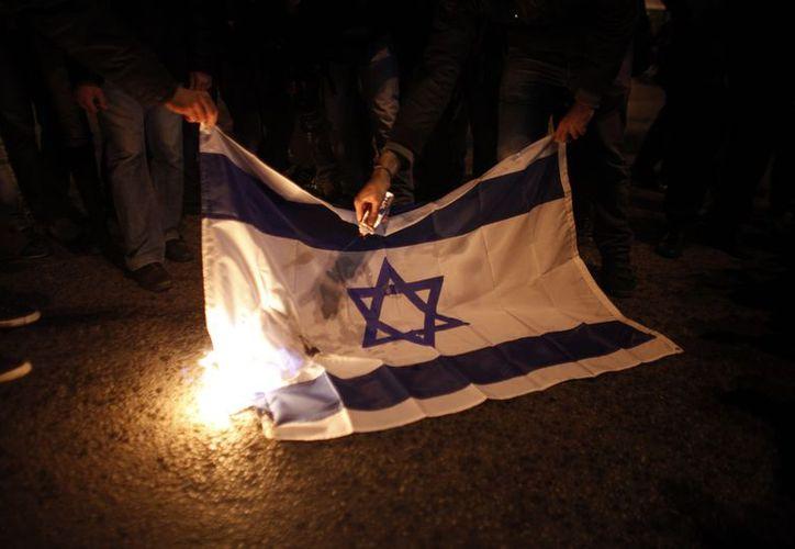Manifestantes queman una bandera de Israel en la Franja de Gaza, donde la Fuerza hebrea bombardeó esta madrugada el cuartel de Hamas. (Agencias)