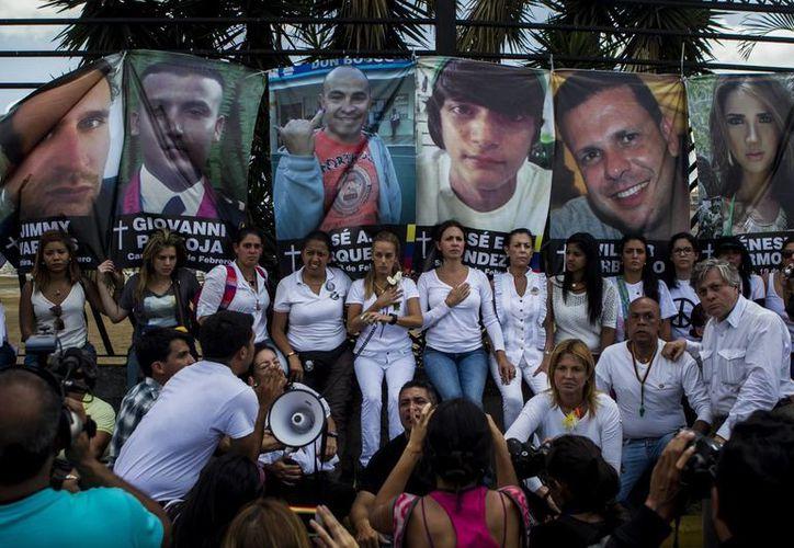 Los rostros de las 18 víctimas mortales en protestas fueron colgadas en el aeropuerto La Carlota de Caracas. (EFE)
