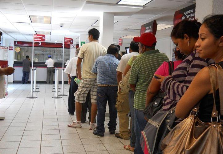 La larga fila de empleados municipales , que se dieron cita en la sucursal de Banorte de la avenida Héroes, denotaba lo que estaba sucediendo.  (Ernesto Neveu/SIPSE)