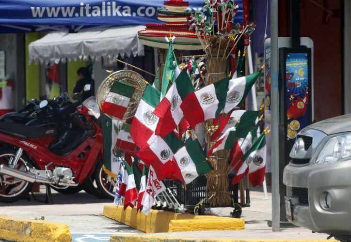 Los vendedores esperan que sus productos, en colores verde, blanco y rojo, atraigan las compras durante los próximos días y hasta el 15 de septiembre. (Harold Alcocer/SIPSE)