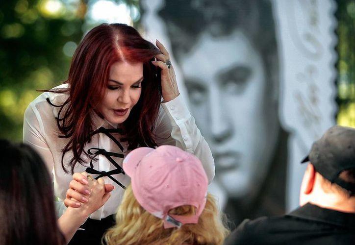 En la imagen, Priscilla Presley saluda a seguidores de Elvis, Dawn and Phillip Pratt tras una presentación del nuevo sello de Elvis Forever, el segundo sello postal el icono de la música. (AP)