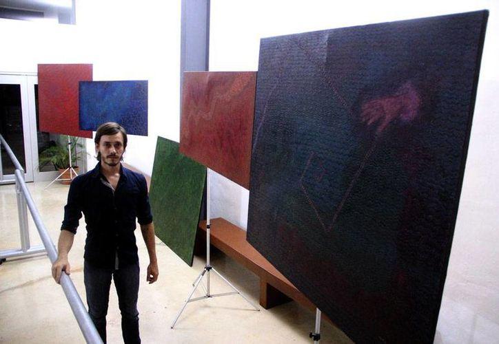 """Matt Denegrevaught presenta obra 'unipersonal' Conciencia es... Existencia"""". Los cuadros con los que aparece en la imagen son parte de la obra. (José Acosta/SIPSE)"""
