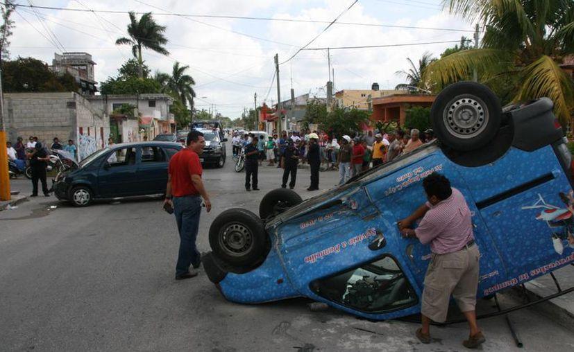 El choque provoca la volcadura de un vehículo de reparto de una lavandería. (Irving Canul/SIPSE)