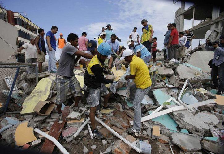 Numerosos hombres ayudan a rescatar a los atrapados entre los escombros después del terremoto de magnitud 7.8 en la escala de Ritcher que golpeó Ecuador, la noche del sábado (AP)