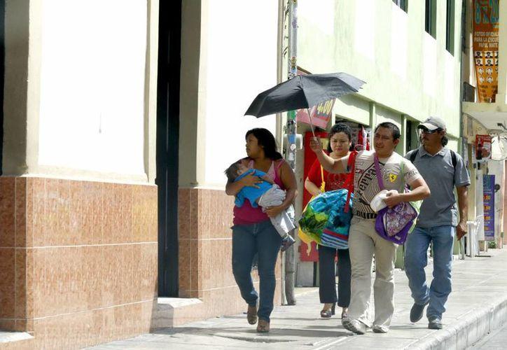 Con gorras o sombrillas, los yucatecos se cubieron ayer del sol. (Christian Ayala/SIPSE)