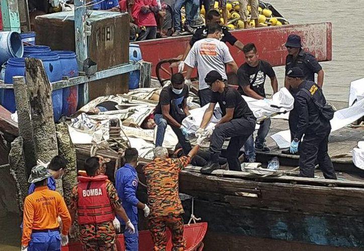 Fotografía facilitada por la Agencia Marítima Malasia que muestra el traslado de los cuerpos sin vida de las víctimas de un naufragio en Perak, Malasia. (EFE/Malaysian Maritime Enforcement)