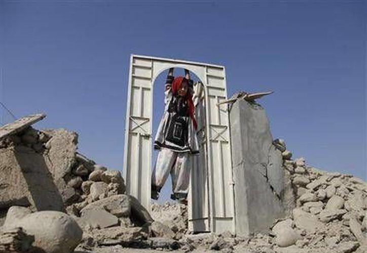 Una niña paquistaní juega en la puerta de una casa destruida el martes por un sismo en el remoto distrito de Awaran, en la provincia de Baluchistán. (Agencias)