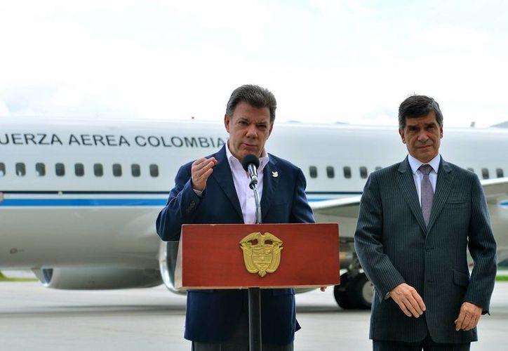 Juan Manuel Santos mientras pronuncia un discurso junto a su ministro de Trabajo, Rafael Pardo, en el aeropuerto militar de CATAM en Bogotá. (Archivo/EFE)