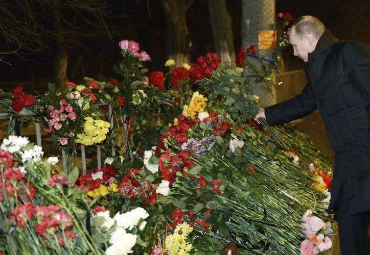 El presidente ruso, Vladimir Putin, deposita unas flores en el sitio del atentado contra un trolebús en Volgogrado. (EFE)