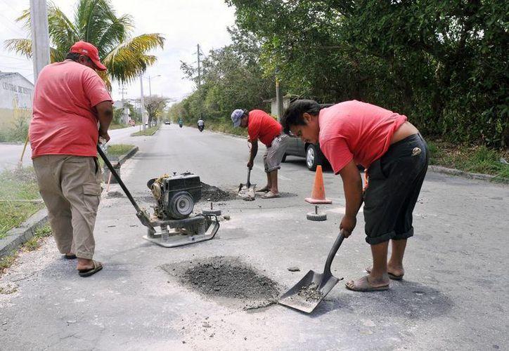 Personal de Servicios Públicos en los trabajos de bacheo. (Cortesía/SIPSE)