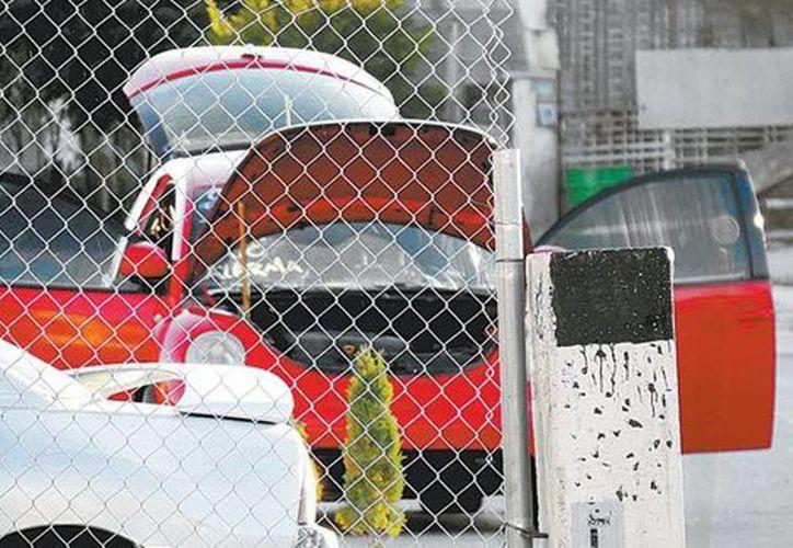Imagen del automóvil rojo en el que se encontró un cargamento de explosivos en la colonia Parajes de San Isidro. (Juan José García/Milenio)