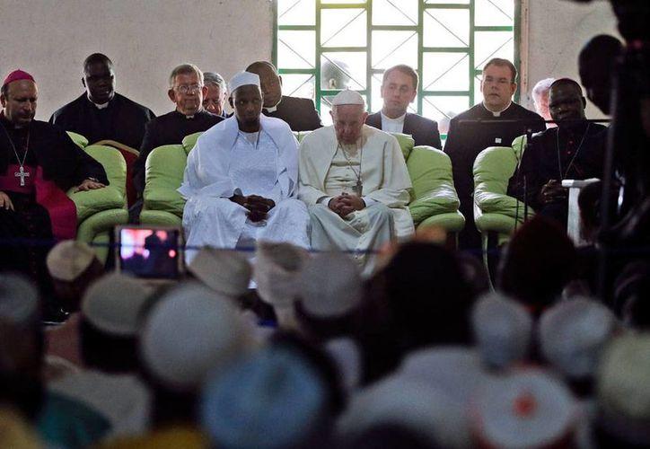 """El Papa Francisco en la mezquita de Bangui, con el principal imán, Tidiani Moussa Naibi, quien calificó la visita del Pontífice como """"un símbolo de que todos nos entendemos"""". (AP/Andrew Medichini)"""