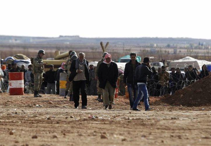 Refugiados sirios esperan para cruzar la frontera y pasar a Turquía cerca de Kobane, Siria. (Archivo/EFE)