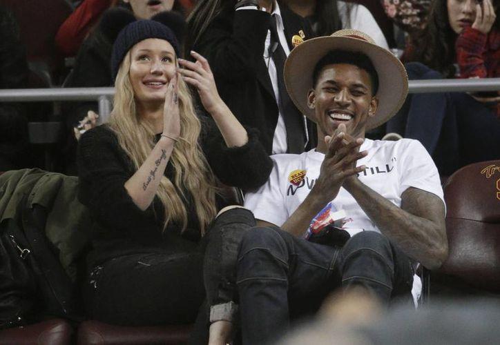La cantante Iggy Azalea anunció su compromiso matrimonial con el jugador de la NBA, Nick Young. Ambos aparecen juntos en esta foto de enero del año en curso, durante un partido de basquetbol colegial en Los Angeles. (Foto: AP)