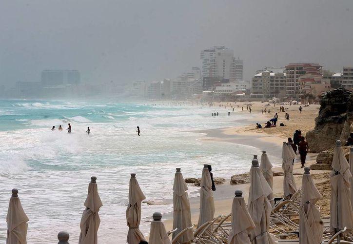 Turistas disfrutan de las playas de Cancún, pese al mal tiempo. (Notimex)