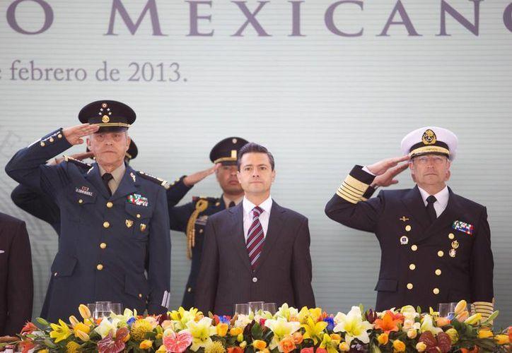 El presidente Enrique Peña Nieto flanqueado por los secretarios de Defensa y Marina durante la ceremonia del Día del Ejército, ayer en Edomex. (Notimex)