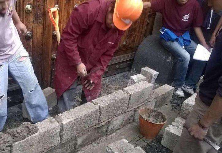Frente a las instalaciones de la SEP construyen un muro con tabiques y cemento que llevaron los manifestantes del IPN. (Ana Paola Wong/Milenio)