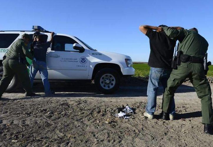 Imagen de archivo de agentes de la patrulla fronteriza al detener a dos inmigrantes. (Archivo/EFE)