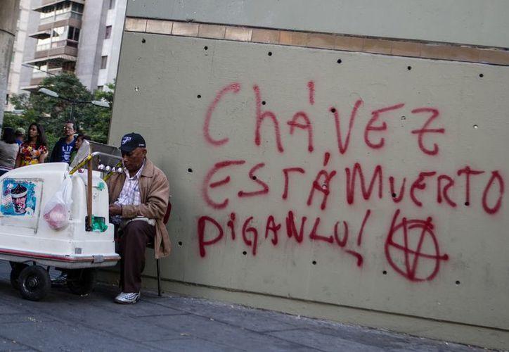 Un hombre vende helados cerca de un graffiti que especula con la muerte de Hugo Chávez, en Caracas. (EFE)