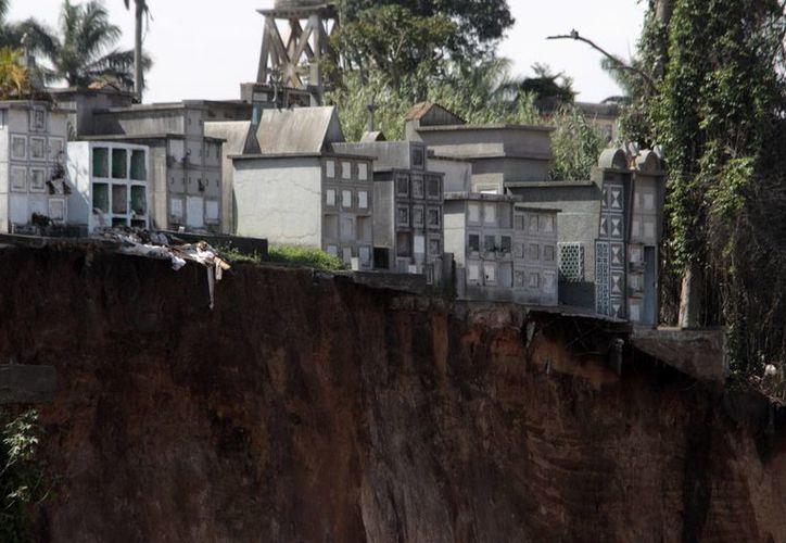 Varios derrumbes se han llevado decenas de tumbas; las familias desean recuperar los restos de sus seres queridos. (EFE)