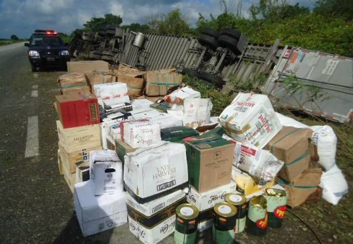 Cientos de cajas con botellas de costosas bebidas quedaron tiradas en la carretera al volcar de tráiler. (Milenio Novedades)