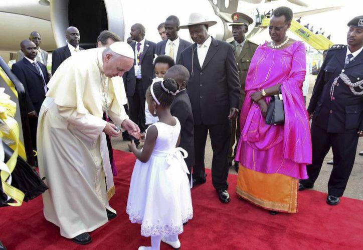El Papa Francisco saluda a unos niños que le dieron la bienvenida el viernes 27 de noviembre de 2015 en el aeropuerto internacional de Entebbe; a la derecha (con sombrero), el presidente de Uganda, Yoweri Museveni. (AP)