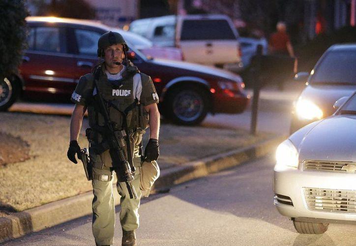 Un oficial de policía abandona la casa donde estaban los rehenes y su victimario. (Agencias)
