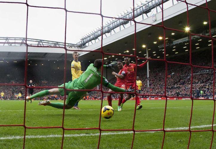 Raheem Sterling, del Liverpool, anota su primer gol frente a Wojciech Szczesny, del Arsenal, que vivió una auténtica pesadilla como visitante. (Agencias)